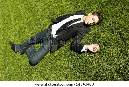 Businessman resting over the grass - stock photo