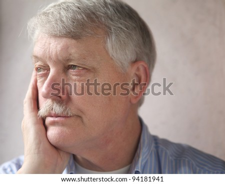 businessman rests his head on his hand, looks irritated - stock photo