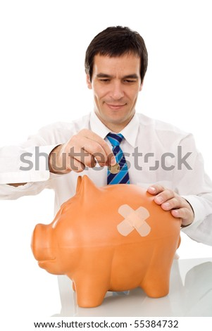 Businessman resuming savings - putting coin in wounded piggy bank - isolated