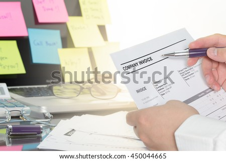 Businessman review his company invoice on tangle office desk for made a payment. - stock photo