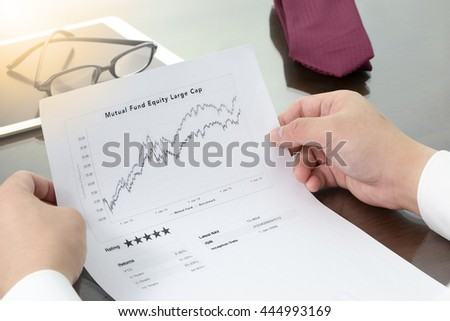 Businessman review  his mutual fund return and benchmark graphs and mutual fund rating. Mutual fund information with pen. - stock photo