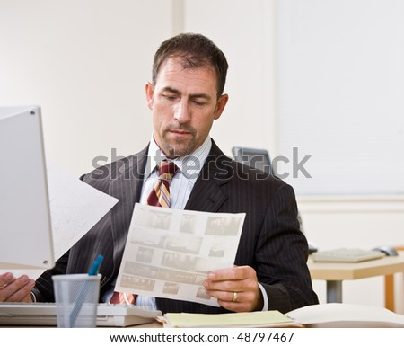 Businessman reviewing paperwork - stock photo