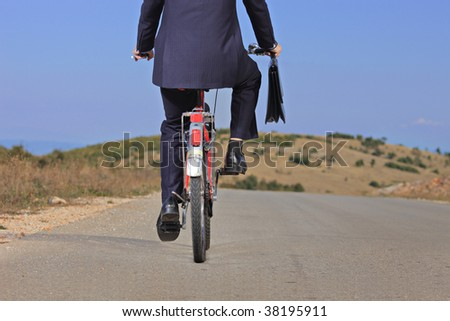 Businessman riding a bike outdoors - stock photo