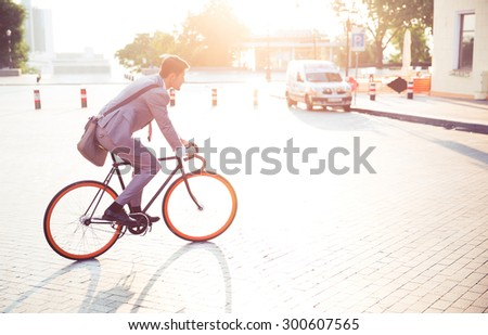 Businessman riding bicycle to work in town  - stock photo