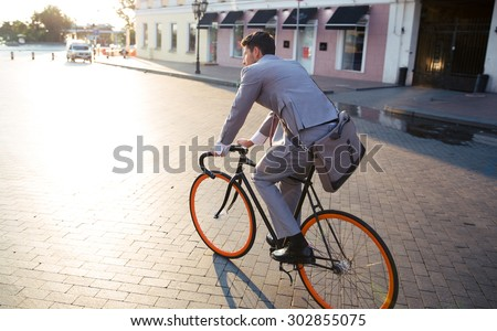 Businessman riding bicycle to work on urban street in morning - stock photo