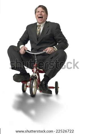 Businessman riding child's tricycle - stock photo