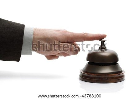 Businessman ringing a hotel reception service bell to request assistance - stock photo