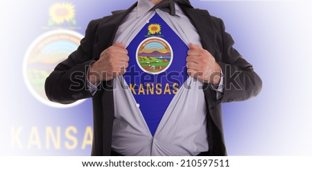 Businessman rips open his shirt to show his Kansas flag t-shirt - stock photo