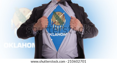 Businessman rips open his shirt to show his oklahoma flag t-shirt - stock photo