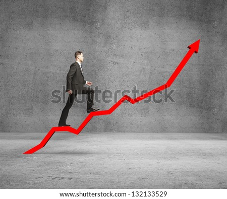 businessman rise on chart on concrete room - stock photo
