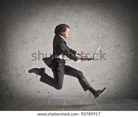Businessman running and carrying a laptop - stock photo