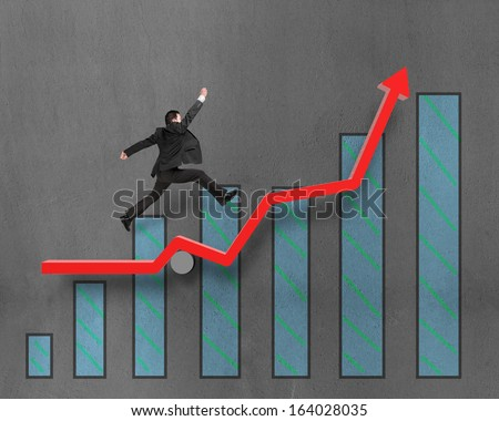 Businessman running and jumping on growth red arrow with chart in concrete wall background - stock photo