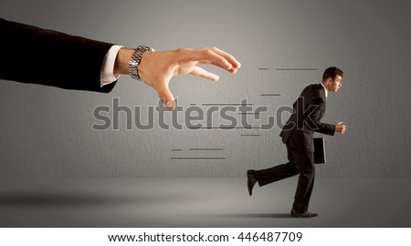 Businessman running away from a huge hand concept on background - stock photo