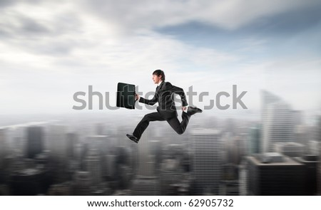 Businessman running fast over a city - stock photo