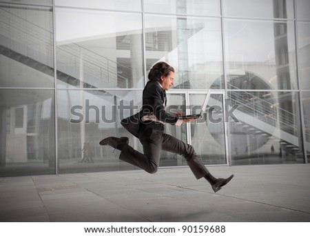 Businessman running fast with office building in the background