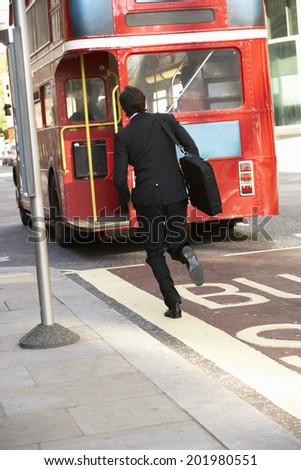 Businessman running for bus - stock photo