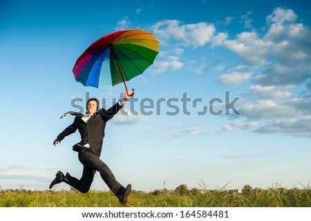 Businessman running in a green field with multicolored umbrella.