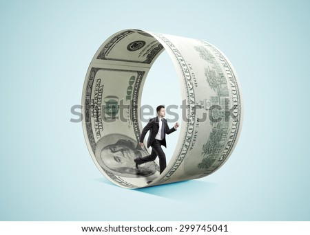 businessman running in money wheel  on blue background - stock photo