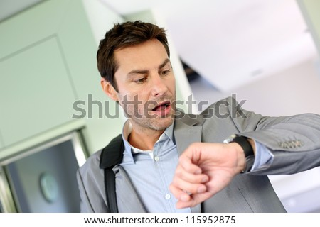 Businessman running late for work - stock photo