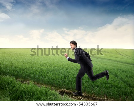 Businessman running on a countryside path - stock photo