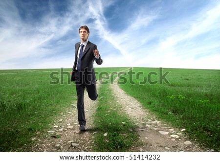 Businessman running on a countryside road - stock photo