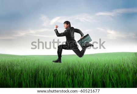 Businessman running on a green meadow - stock photo