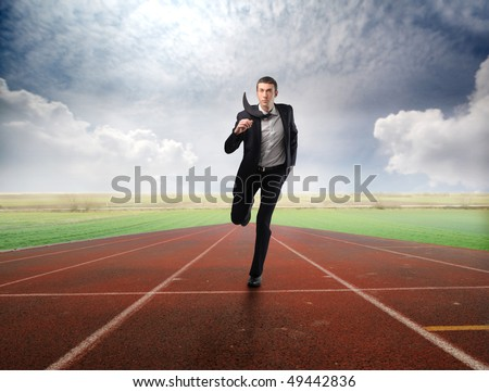 Businessman running on a racing track - stock photo