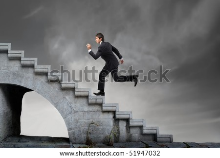 Businessman running on a stairway - stock photo