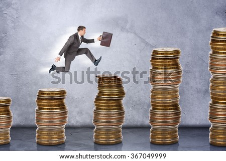 Businessman running on stack of coins