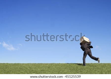 Businessman running over field in countryside carrying cardboard box, blue sky background.