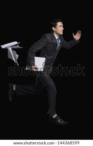 Businessman running with a clipboard - stock photo