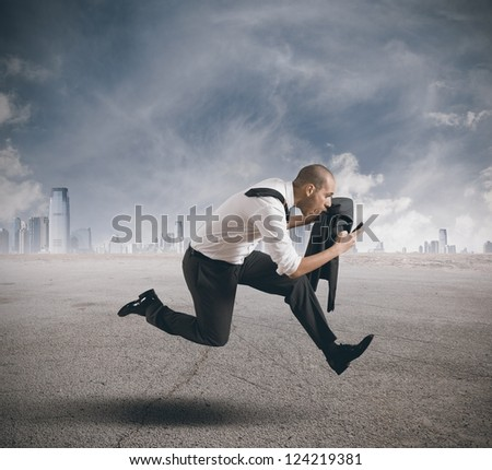 Businessman running with mobile phone in hand - stock photo