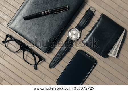 Businessman's accessories, black leather book, pen, wristwatch, wallet with money, smart phone, glasses, on a bamboo background - stock photo