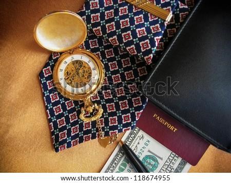 Businessman's accessories including pocket watch, pen, wallet, passport, money, stickpin and necktie. - stock photo