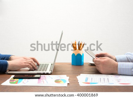 Businessman's at workplace use different devices at one table - stock photo