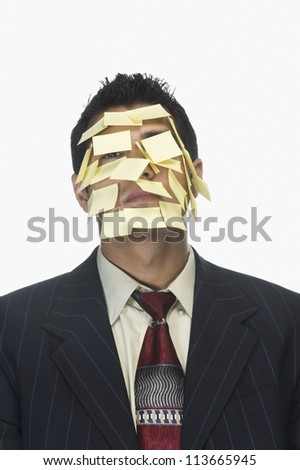 Businessman's face wrapped with adhesive notes - stock photo