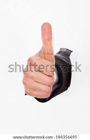 Businessman's hand breaking through white paper wall gesturing thumbs up - stock photo