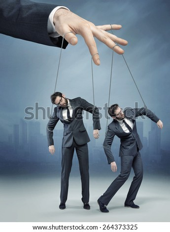 Businessman's hand controlling a worker - stock photo