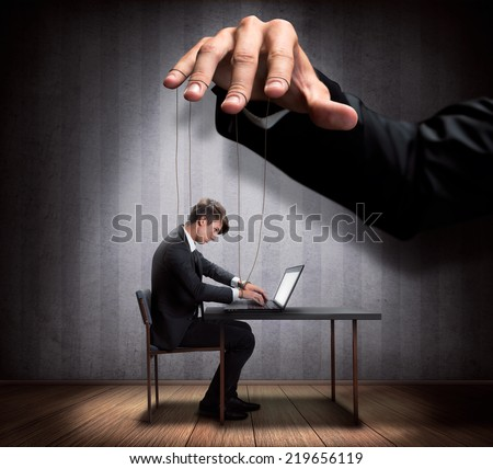 Businessman's hand controlling a worker marionette - stock photo