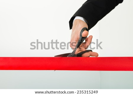 Businessman's hand cutting red ribbon with scissors over white background - stock photo