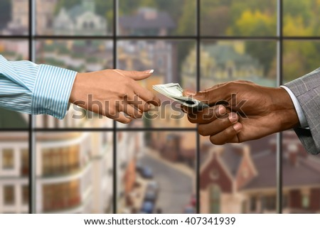 Businessman's hand gives girl cash. Currency transfer on urban background. Just a small bonus. Manager's share from new deal. - stock photo