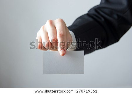 Businessman's hand holding blank business card  pass ticket on a grey background. Copy space for text. - stock photo