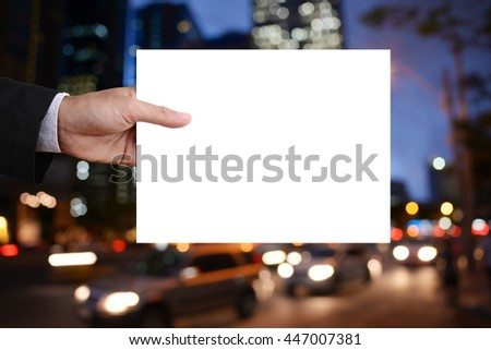 Businessman's hand holding blank cardboard, white paper, poster, frame, advertisement card, banner in front of nightlife in capital background.  - stock photo