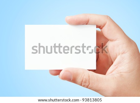 Businessman's hand holding blank paper business card, closeup over light blue background
