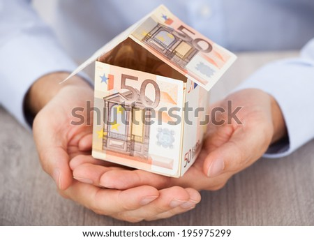 Businessman's hand holding house made of euro notes on table - stock photo