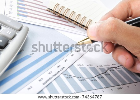 Businessman's hand holding pen over Business background - stock photo