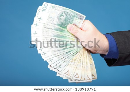 Businessman's hand holding polish money banknote blue background