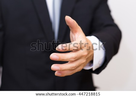 Businessman's hand sending for shake sign in black suit on white background