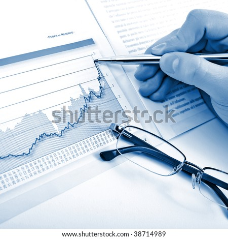 Businessman's hand showing diagram on financial report with pen. Blue business background
