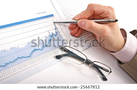Businessman's hand showing diagram on financial report with pen. Business background - stock photo